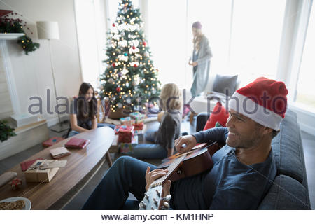 Smiling father in Santa hat playing guitar while family wraps gifts in living room with Christmas tree - Stock Photo