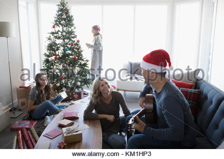 Family playing guitar and wrapping gifts, decorating Christmas tree in living room - Stock Photo
