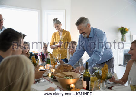 Man serving Thanksgiving turkey to family and friends at dinner table - Stock Photo