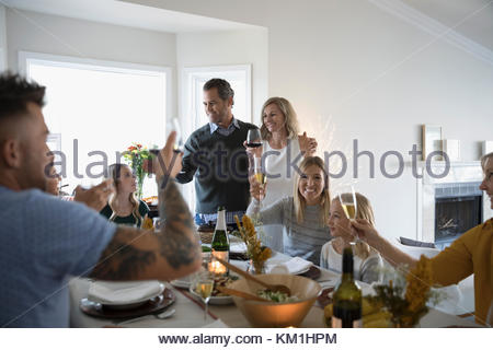 Family and friends toasting champagne and wine glasses at Thanksgiving dinner table - Stock Photo