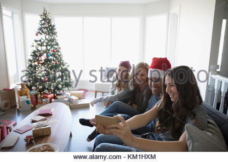 Family with camera phone taking selfie in Christmas living room - Stock Photo