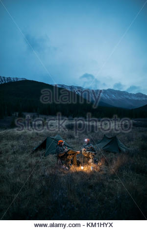 Male hunter friends in camouflage and headlamps at campsite in remote field below mountains at night - Stock Photo