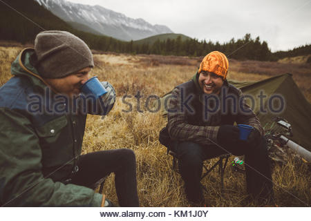 Smiling male hunter friends drinking coffee outside tent at campsite in remote field below mountains - Stock Photo