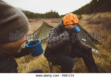 Male hunter friends drinking coffee outside tents at campsite in remote field - Stock Photo
