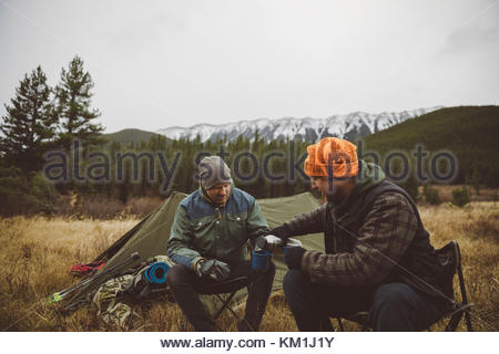 Male hunter friends drinking coffee outside tents at campsite in remote field below mountains - Stock Photo