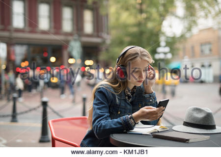 Blonde young woman with headphones listening to music with smart phone at urban sidewalk cafe - Stock Photo