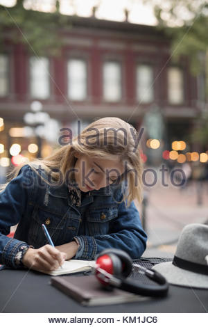 Blonde young woman writing in journal at sidewalk cafe - Stock Photo