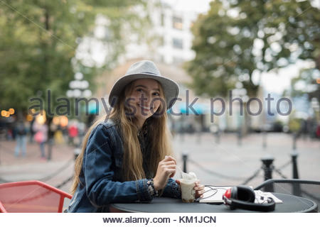 Portrait smiling young woman eating ice cream at urban sidewalk cafe - Stock Photo