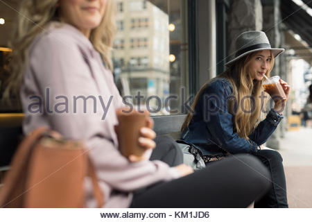 Young women friends drinking iced coffee on bench at sidewalk cafe - Stock Photo