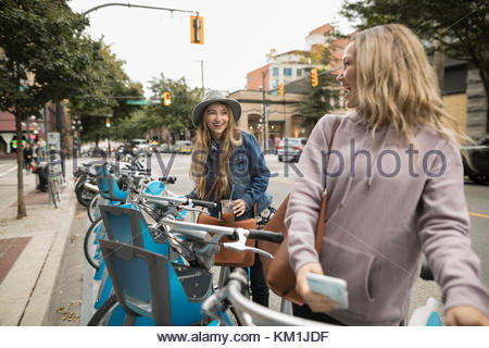 Young women friends using bicycle sharing system on urban street - Stock Photo