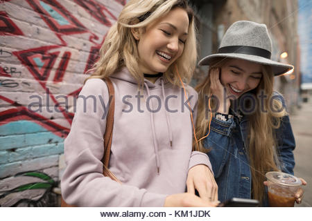 Smiling young women friends drinking iced coffee and texting with smart phone - Stock Photo