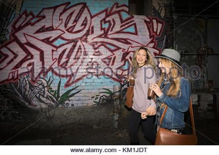 Young women friends drinking iced coffee, walking along urban graffiti wall - Stock Photo