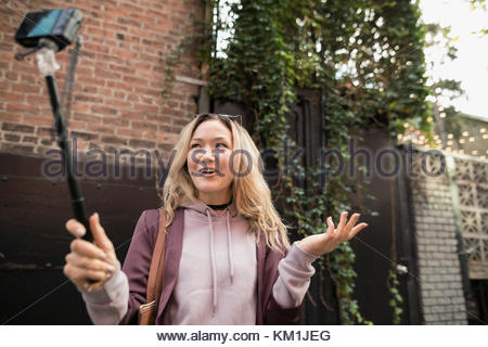Young woman taking selfie with camera phone on selfie stick - Stock Photo