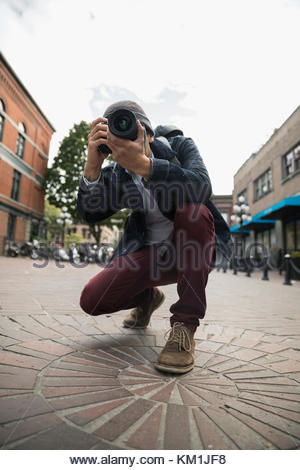 Man with digital camera photographing on urban street - Stock Photo
