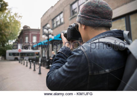 Man with digital camera photographing urban street - Stock Photo