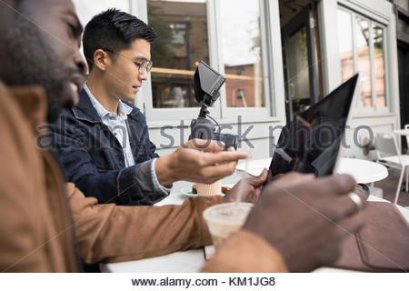 Men friends vlogging, watching video on digital camera at sidewalk cafe - Stock Photo