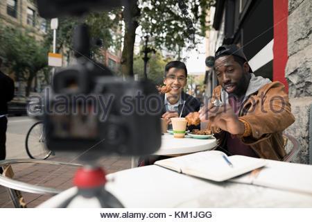 Men vlogging with video camera, eating at urban sidewalk cafe - Stock Photo