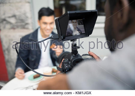 Man vlogging, videoing friend eating at sidewalk cafe with video camera - Stock Photo