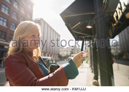 Mature woman with coffee using camera phone at sunny urban window storefront - Stock Photo