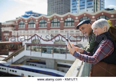 Senior couple tourists using smart phone on sunny urban rooftop - Stock Photo