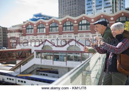 Senior couple tourists using camera phone on sunny urban rooftop - Stock Photo