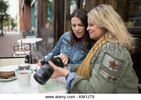 Mature women looking at digital camera viewfinder at sidewalk cafe - Stock Photo