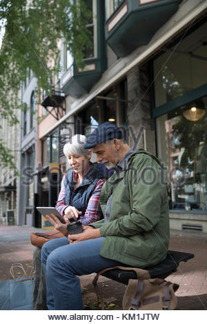 Senior couple using digital tablet on urban bench - Stock Photo