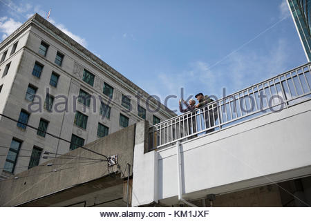 Senior couple tourists using camera phone on sunny urban bridge - Stock Photo