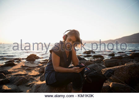 Woman with hiking backpack relaxing, listening to music with headphones on sunny ocean beach - Stock Photo