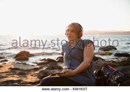 Woman relaxing, listening to music with headphones on sunny ocean beach - Stock Photo
