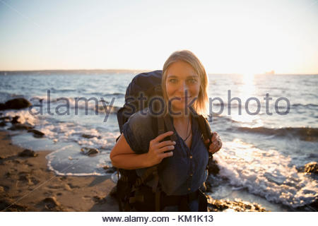 Portrait smiling woman with hiking backpack on sunny ocean beach - Stock Photo