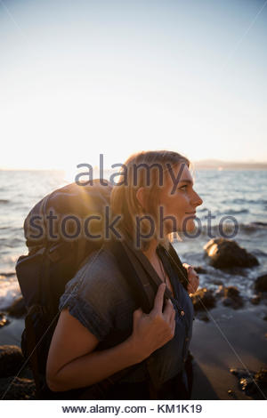 Pensive woman with hiking backpack walking on sunny ocean beach - Stock Photo
