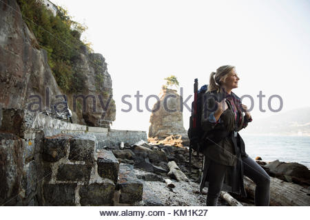 Smiling woman with hiking backpack on beach rocks - Stock Photo