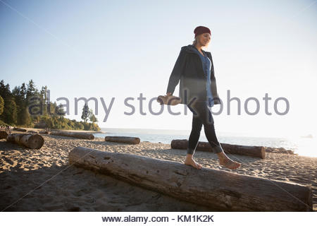 Barefoot woman walking, balancing on log on sunny ocean beach - Stock Photo