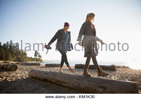 Mother and daughter walking, balancing on log on sunny ocean beach - Stock Photo