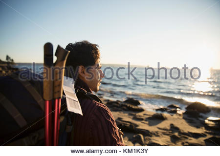 Man with hiking backpack looking at sunny ocean view - Stock Photo
