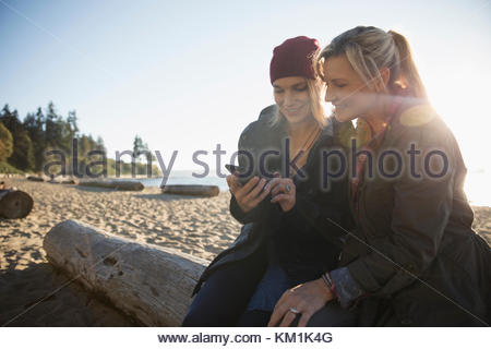 Mother and daughter using smart phone on sunny ocean beach - Stock Photo