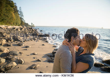 Affectionate couple kissing on sunny ocean beach - Stock Photo