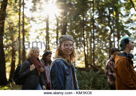 Portrait smiling girl hiking in woods with family - Stock Photo