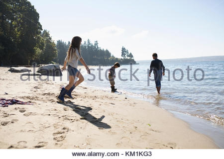 Boy and girl friends playing on sunny ocean beach - Stock Photo