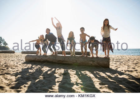 Exuberant boy and girl friends jumping off log on sunny ocean beach - Stock Photo