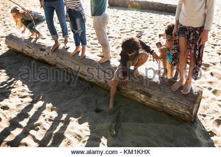 Boy and girl friends on log on sunny beach - Stock Photo