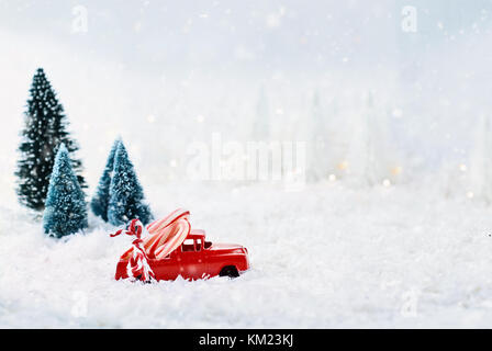 1950's antique vintage red truck hauling a candy canes home through a snowy winter wonder land with pine trees in - Stock Photo