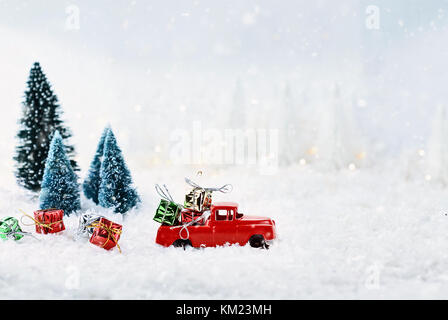 1950's antique vintage red truck hauling a Christmas gifts home through a snowy winter wonder land with pine trees. - Stock Photo