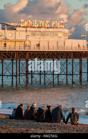 Young people sitting on Brighton beach in the setting sun, East Sussex, England. - Stock Photo