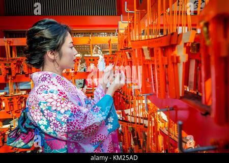Women in traditional japanese kimonos at Fushimi Inari Shrine in Kyoto, Japan - Stock Photo