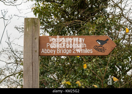 Signpost on the Teesdale Way long distance footpath showing a distance of 2 3/4 miles to Abbey Bridge. December - Stock Photo