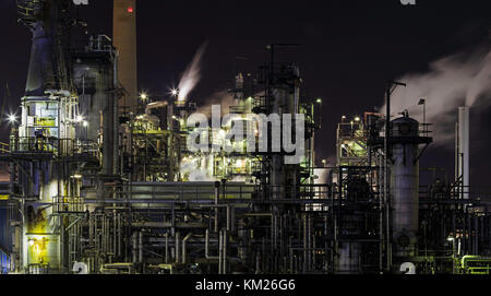 Closeup of oil refinery plant at night - Stock Photo