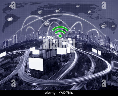 Network connection line between building over the top view of cityscape with the Elevated highway and world map - Stock Photo