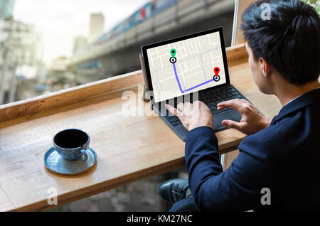 Businessman sitting and using computer laptop showing part of navigator map for choosing the direction on traffic - Stock Photo